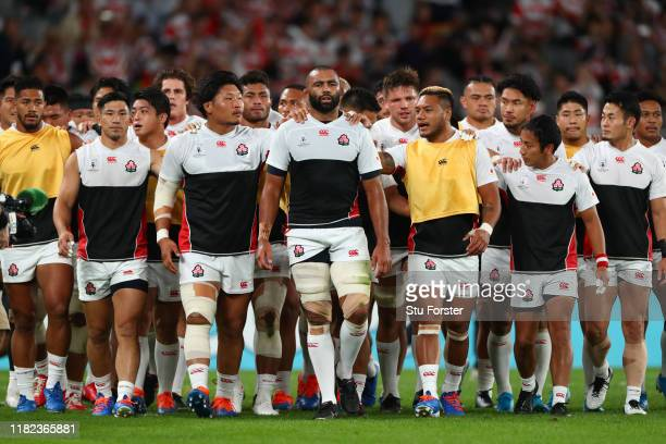 Captain Michael Leitch of Japan leads his team off the field arm in arm after the warm up before the Rugby World Cup 2019 Quarter Final match between...