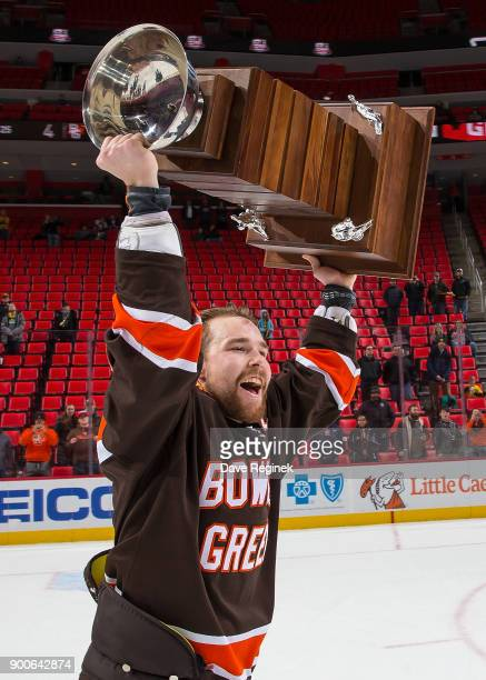 Captain Mitchell McLain of the Bowling Green Falcons lifts the John MacInnes Cup after winning the championship game of the Great Lakes Invitational...