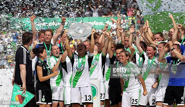 Captain Nadine Kessler of VfL Wolfsburg lifts the trophy in celebration alongsaide team mates after the Women's Bundesliga match between VfL...