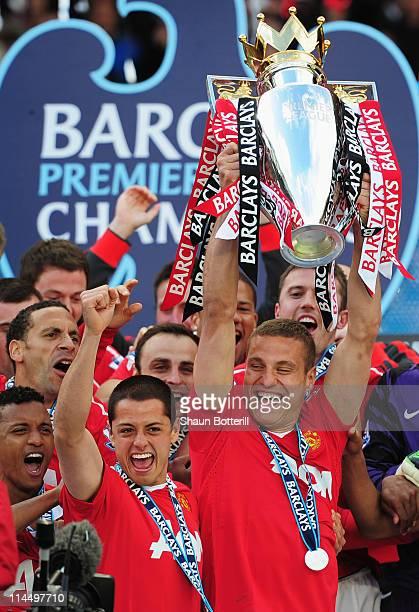 Captain Nemanja Vidic of Manchester United lifts the Premier League trophy alongside Javier Hernandez after the Barclays Premier League match between...