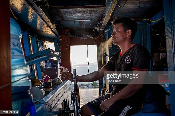 Captain Nguyen Cho 47 leftside smokes and supervies his workers on Tho Quang fishing port after a fishing trip he said 'we use to work peacefully...
