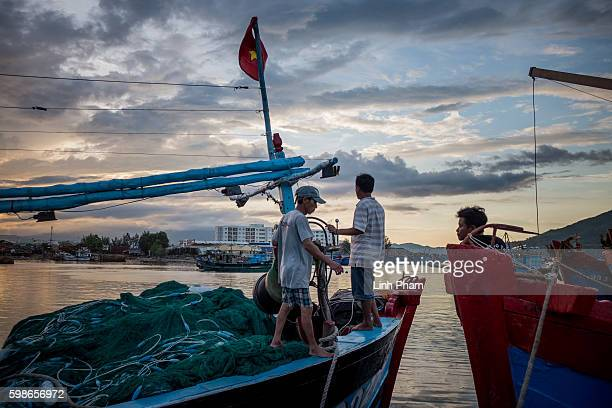 Captain Nguyen Cho, 47 - on the far right, greets his friends' boat as they head out of the port on Tho Quang fishing port, he said 'we use to work...