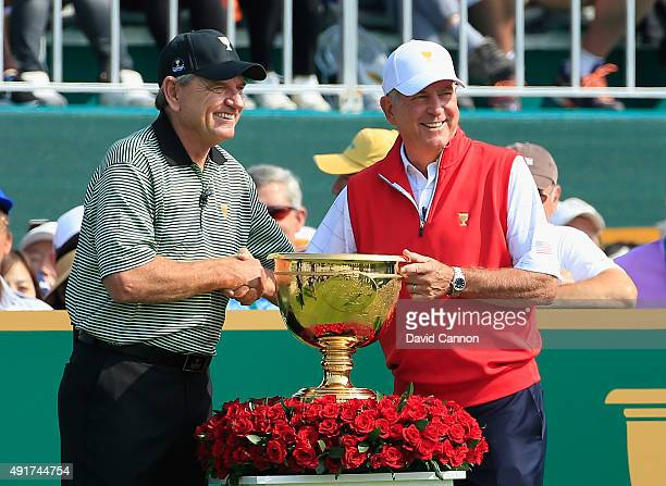 Captain Nick Price of the International Team shakes hands on the first tee with Captain Jay Haas of the United States Team during the Thursday...