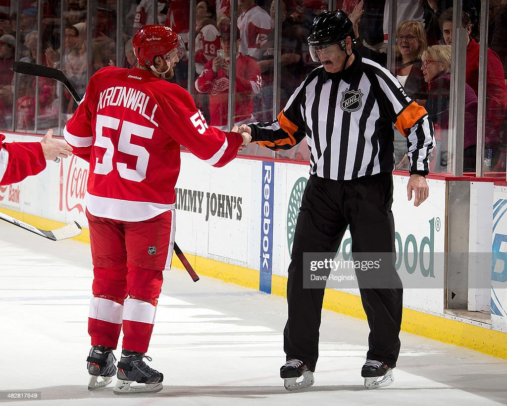 Captain Niklas Kronwall #55 of the Detroit Red Wings shakes referee Don Van Massenhoven #21's hand after his final NHL game against the Buffalo Sabres on April 4, 2014 at Joe Louis Arena in Detroit, Michigan. Detroit defeated Buffalo 3-2