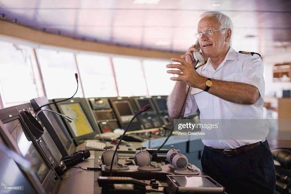 Captain of a ship having a phone call : Stock Photo