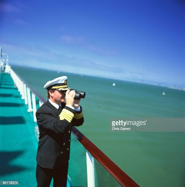 Captain of cruise ship using binoculars