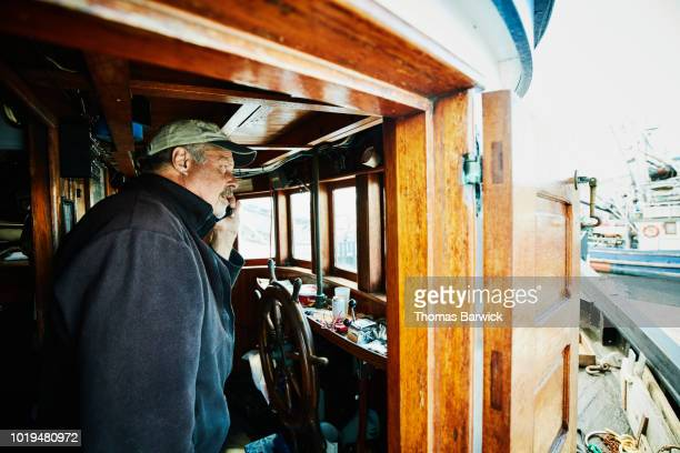 Captain of fishing boat talking on smart phone in wheelhouse while preparing boat for fishing trip