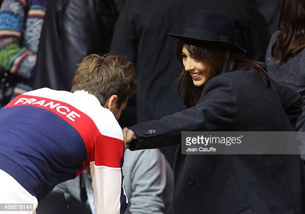 Captain of France Arnaud Clement kisses the hand of his girlfriend singer Nolwenn Leroy after day one of the Davis Cup tennis final between France...
