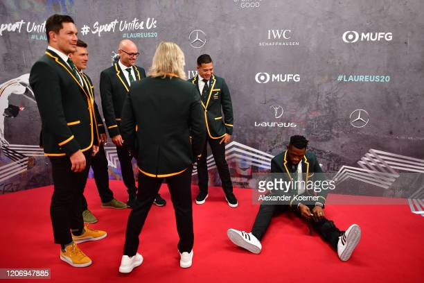 Captain of Laureus World Team of the Year the South Africa Men's Rugby Team Siya Kolisi fixes his knee guard as his fellow teammates Francois Louw...