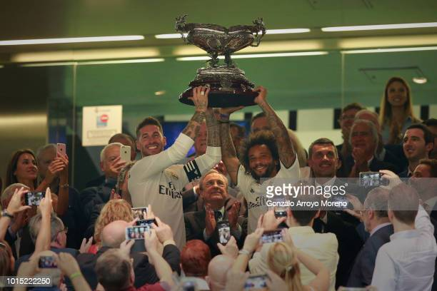 Captain of Real Madrid Sergio Ramos and his teammate Marcelo stand the Santiago Bernabéu Trophy ahead their president Florentino Perez after winning...