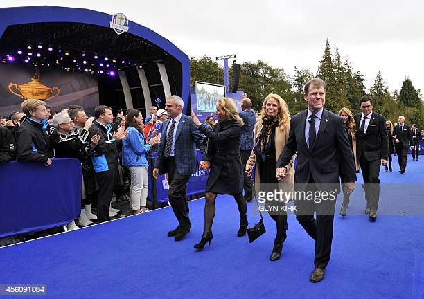 Captain of Team Europe Paul McGinley of Ireland and his wife Alison walk with US Team Captain Tom Watson and his wife Hilary following the opening...