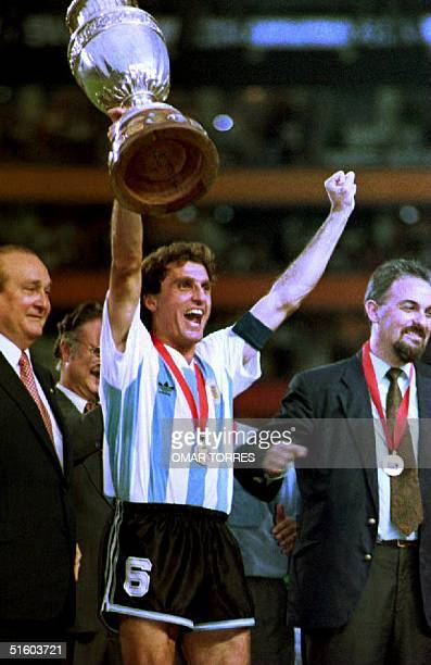 Captain of the Argentine soccer team Oscar Ruggeri holds the Copa America championship trophy high as he celebrates 04 July 1993 Argentina's 21...