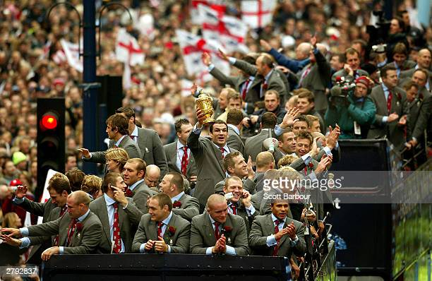 Captain of the England rugby team, Martin Johnson holds the William Webb Ellis trophy aloft during the England Rugby World Cup team victory parade...