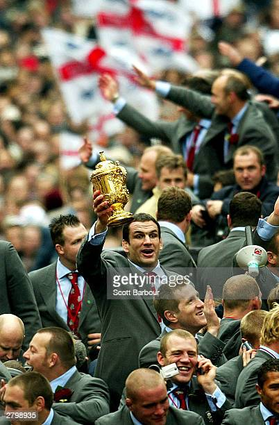 Captain of the England rugby team, Martin Johnson, holds the William Webb Ellis trophy aloft during the England Rugby World Cup team victory parade...