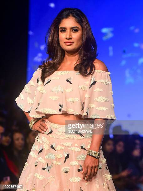 Captain of the Indian women's national cricket team, Mithali Raj, presents a creation by designer Payal Singhal during the Lakme Fashion Week 2020...