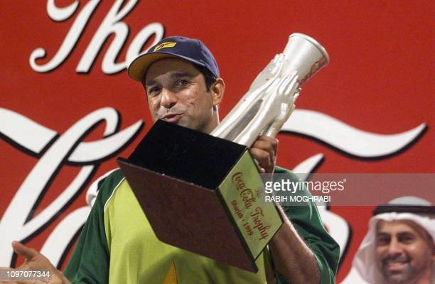 Captain of the Pakistani cricket team, Wasim Akram, holds the Coca Cola trophy late 22 October 1999 after his team won the Sharjah Cup final by...