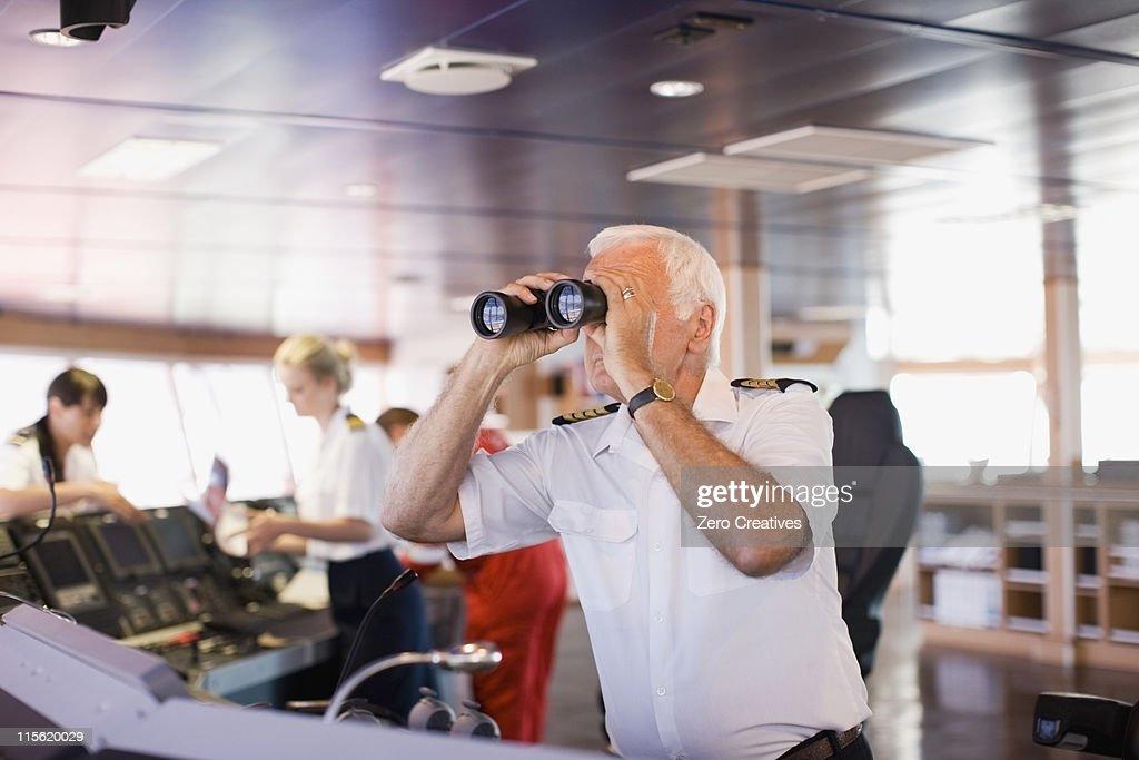 Captain on ship looking through a telescope : Stock Photo