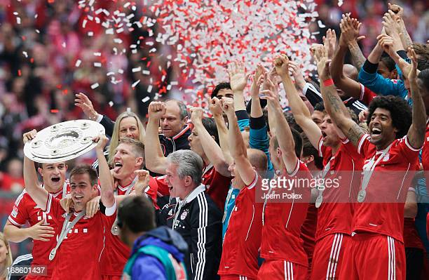 Captain Philipp Lahm celebrates with FC Bayern Muenchen team mates as they receive the championship trophy after the Bundesliga match between FC...
