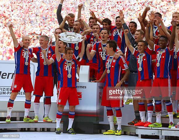 Captain Philipp Lahm of Bayern Muenchen lifts the Bundesliga championship trophy in celebration after the Bundesliga match between Bayern Muenchen...