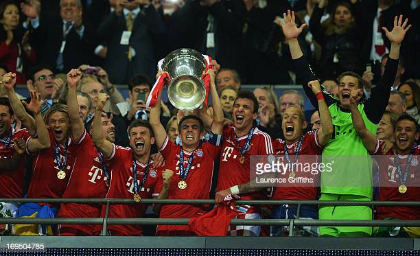 Captain Philipp Lahm of Bayern Muenchen lifts the trophy in celebration after victory in the UEFA Champions League final match between Borussia...