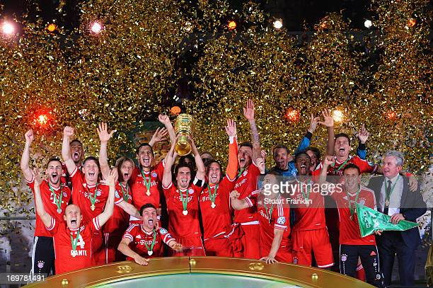 Captain Philipp Lahm of Bayern Muenchen lifts the trophy with team mates to celebrate victory after the DFB Cup Final match between FC Bayern...
