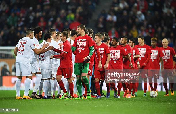 Captain Philipp Lahm of Bayern Munich and his team wear tshirts showing support for injured team mate Holger Badstuber as they shake hands with...