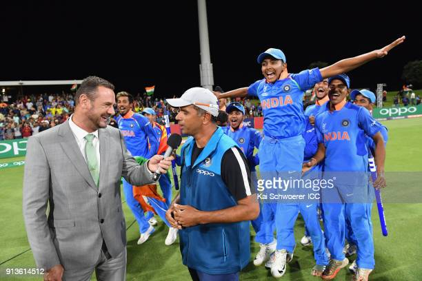 Captain Prithvi Shaw of India and his team mates celebrate as Head Coach Rahul Dravid of India is interviewed by Simon Doull after their win in the...
