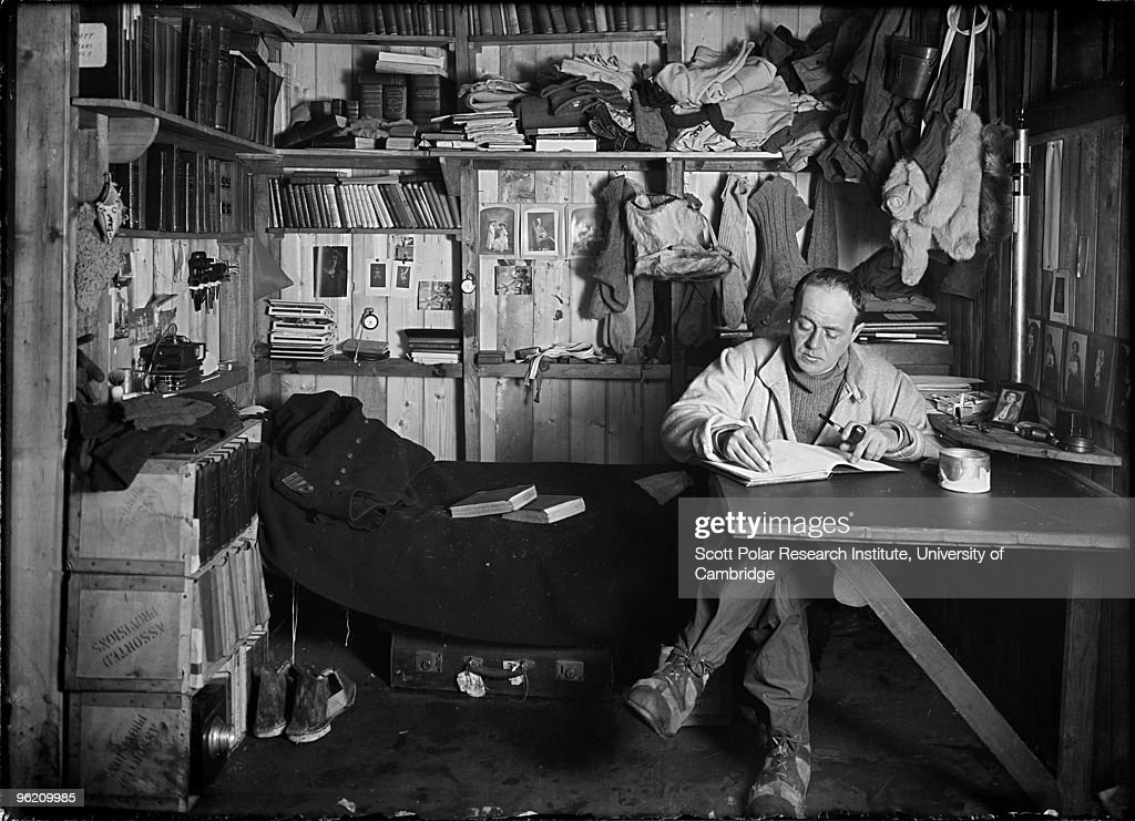 Captain Robert Falcon Scott (1868 - 1912) writes his journal in the Winterquarters Hut, in the Ross Dependency of Antarctica, during his Terra Nova Expedition to the Antarctic, 7th October 1911. Behind him are pictures of his wife and son.