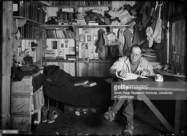 Captain Robert Falcon Scott writes his journal in the Winterquarters Hut in the Ross Dependency of Antarctica during his Terra Nova Expedition to the...