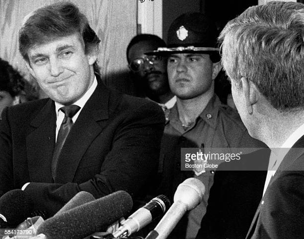 Captain Robert I Smith the pilot of the plane looks to shuttle owner Donald Trump during a press conference in Boston on Aug 10 1989 Smith piloted a...