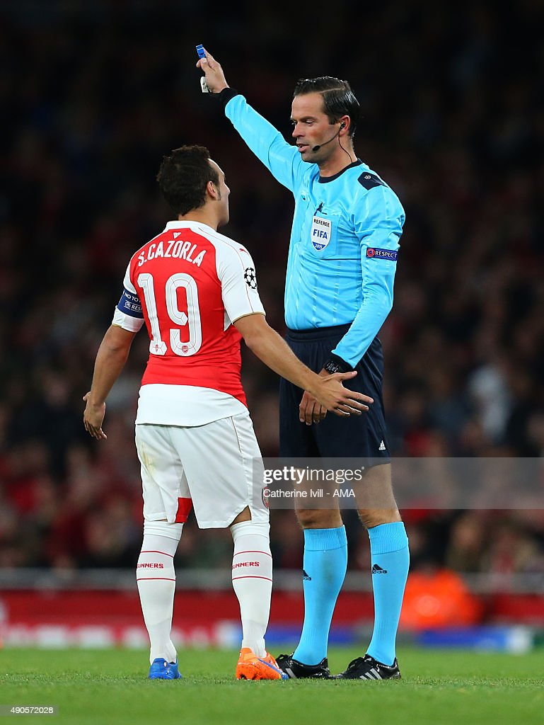 Captain Santi Cazorla of Arsenal talks to Referee Bas Nijhuis during the UEFA Champions League match between Arsenal and Olympiacos at the Emirates Stadium on September 29, 2015 in London, United Kingdom.