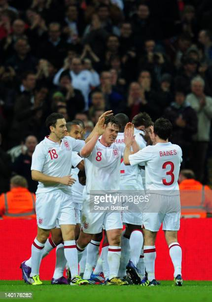 Captain Scott Parker of England celebrates with teammates Stewart Downing and Leighton Baines after Ashley Young of England scored his team's second...