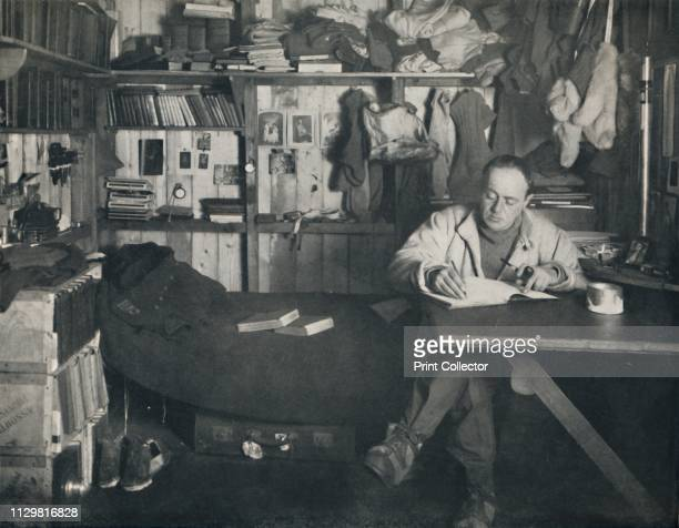 Captain Scott Writing His Diary in the Hut at Cape Evans', circa 1911, . British Antarctic explorer Captain Robert Falcon Scott writing in his...