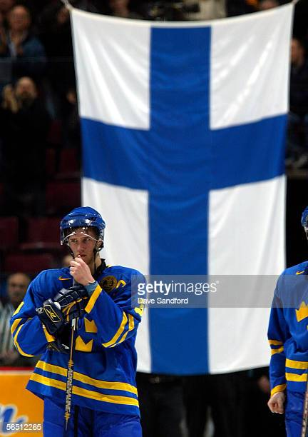 Captain Sebastian Karlsson of Team Sweden stands dejected in front of the Finnish national flag after losing 10 in overtime to Team Finland during...