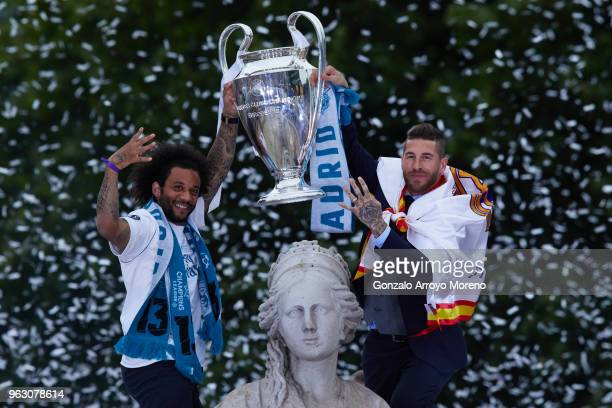 Captain Sergio Ramos of Real Madrid holds up the Champions League trophy with his teammate Marcelo t as they celebrate at Cibeles Square a day after...