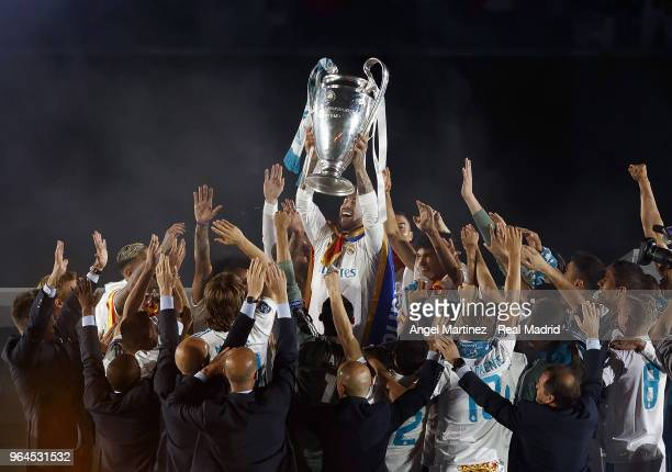 Captain Sergio Ramos of Real Madrid holds up the Champions League trophy with his teammates as they celebrate at Estadio Santiago Bernabeu a day...