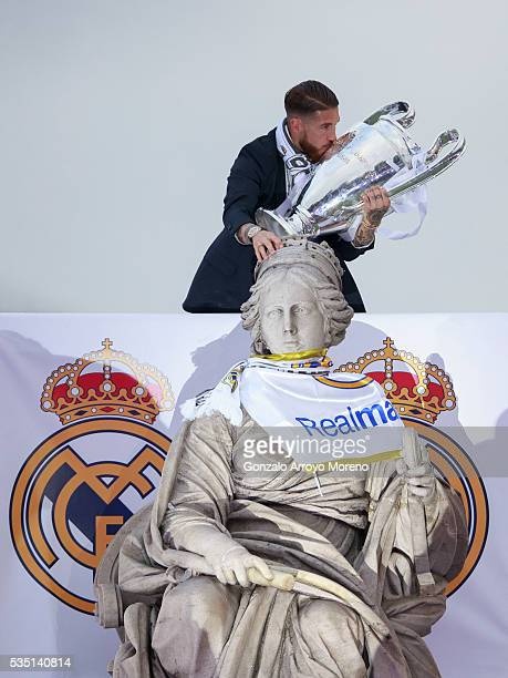 Captain Sergio Ramos of Real Madrid kisses the Trophy as he touches Cibeles font head as he celebrate with his team and fans at Cibeles square after...