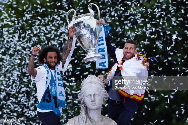 Captain Sergio Ramos of Real Madrid shows the trophy to their fans with his teammate Marcelo t as they celebrate their trophy at Cibeles Square a day...