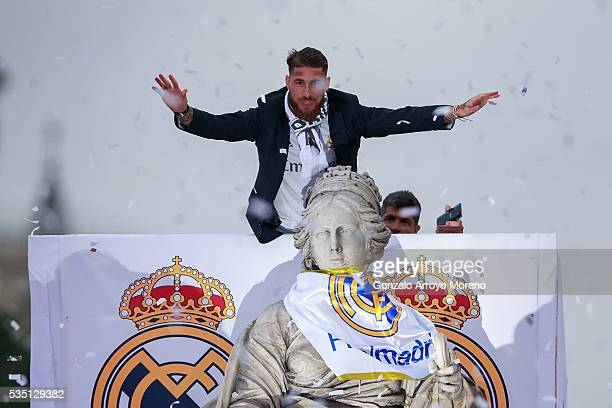 Captain Sergio Ramos of Real Madrid waves the crowd behind Cibeles statue during their team celebration at Cibeles square after winning the Uefa...