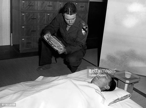 Captain Sewell examines the body of Japanese wartime adviser Prince Fumimaro Konoye after his suicide by poisoning in his Tokyo apartment Konoye was...
