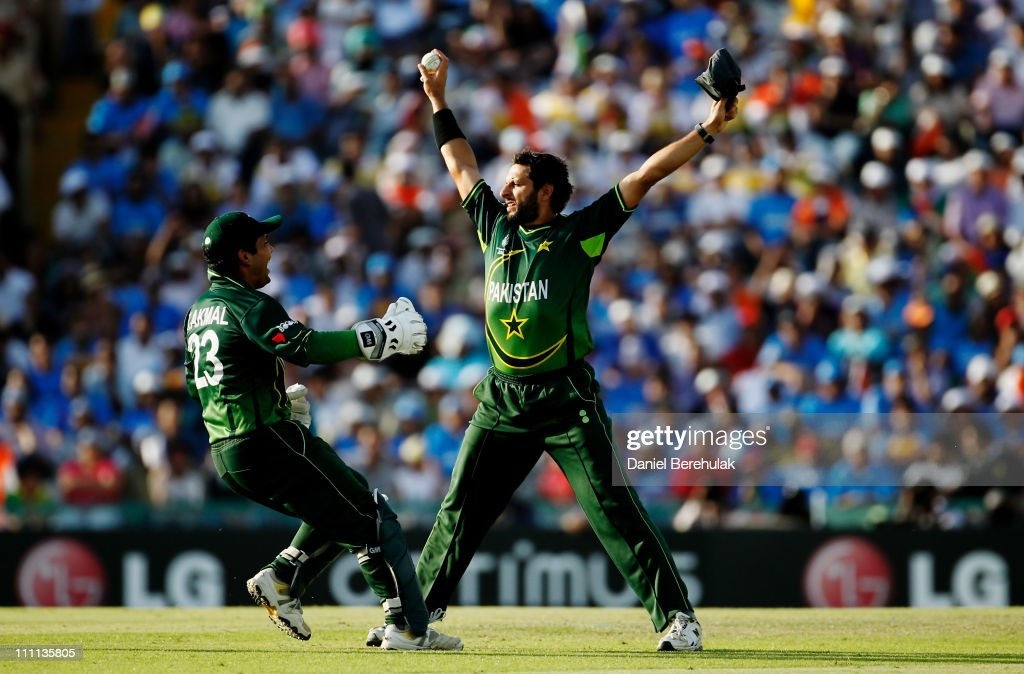 Captain Shahid Afridi of Pakistan celebrates with team mate Kamran Akmal after taking the catch to dismiss Sachin Tendulkar of India off the bowling of Saeed Ajmal of Pakistan during the 2011 ICC World Cup second Semi-Final between India and Pakistan at Punjab Cricket Association (PCA) Stadium on March 30, 2011 in Mohali, India.
