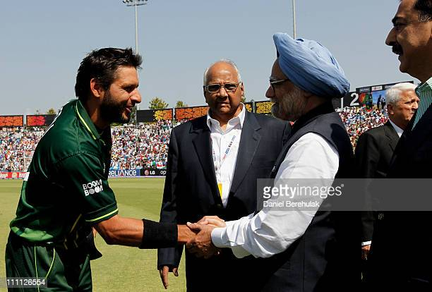 Captain Shahid Afridi of Pakistan shakes hands with Prime Minister Manmohan Singh of India as Prime Minister Syed Yusuf Raza Gilani of Pakistan looks...