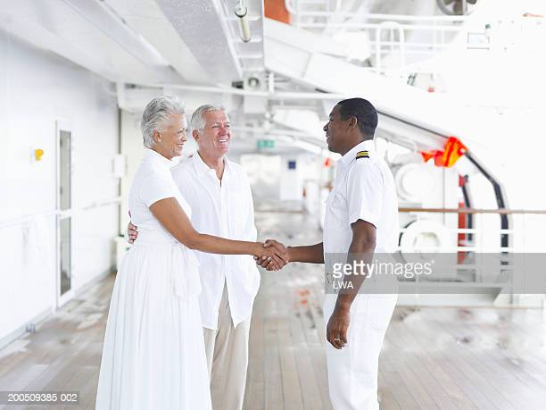 Captain shaking hands with mature couple on deck of cruise ship