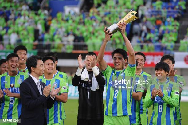 Captain Shunsuke Kikuchi of Shonan Bellmare lifts the trophy as they celerbrate J2 champions and promotion to J1 after the J.League J2 match between...