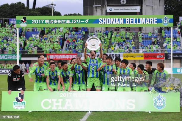 Captain Shunsuke Kikuchi of Shonan Bellmare lifts the trophy as they celerbrate J2 champions and promotion to J1 after the JLeague J2 match between...