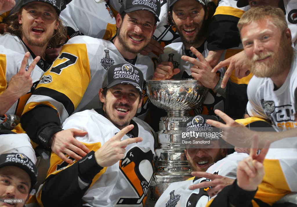 Captain Sidney Crosby #87, Evgeni Malkin #71, Matt Cullen #7, Carl Hagelin #62, Brian Dumoulin #8 and their Pittsburgh Penguins teammates pose for a team photo with the Stanley Cup after Game Six of the 2017 NHL Stanley Cup Final at the Bridgestone Arena on June 11, 2017 in Nashville, Tennessee. The Penguins defeated the Predators 2-0. The Pittsburgh Penguins win the Stanley Cup Final series against the Nashville Predators 4-2.