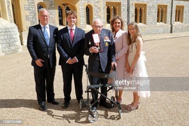 Captain Sir Thomas Moore poses with his family after being awarded with the insignia of Knight Bachelor by Queen Elizabeth II at Windsor Castle on...