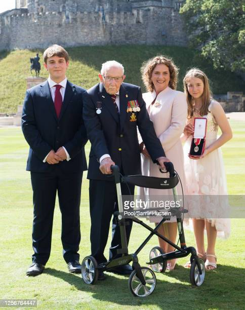Captain Sir Thomas Moore poses with his family after receiving his Knighthood from Queen Elizabeth II during an investiture ceremony at Windsor...