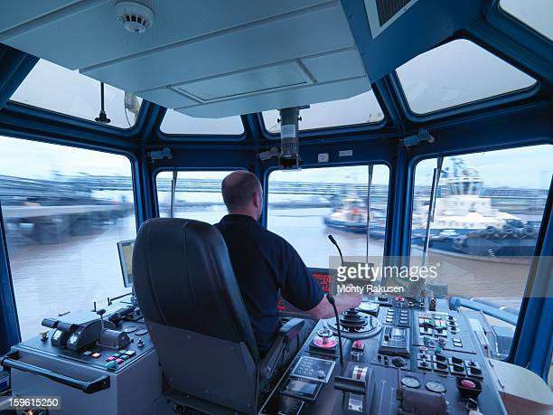Captain steering tug out at sea, view of ships bridge and view through window