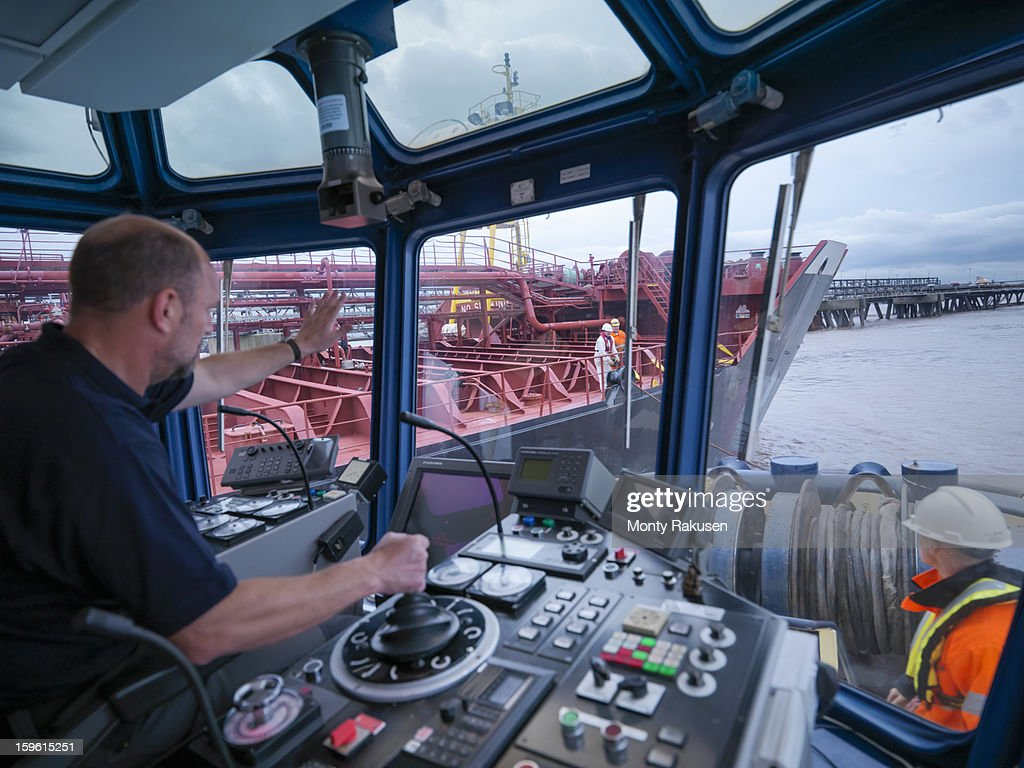 Captain steering tug out at sea, view of ships bridge and view through window : Stock Photo